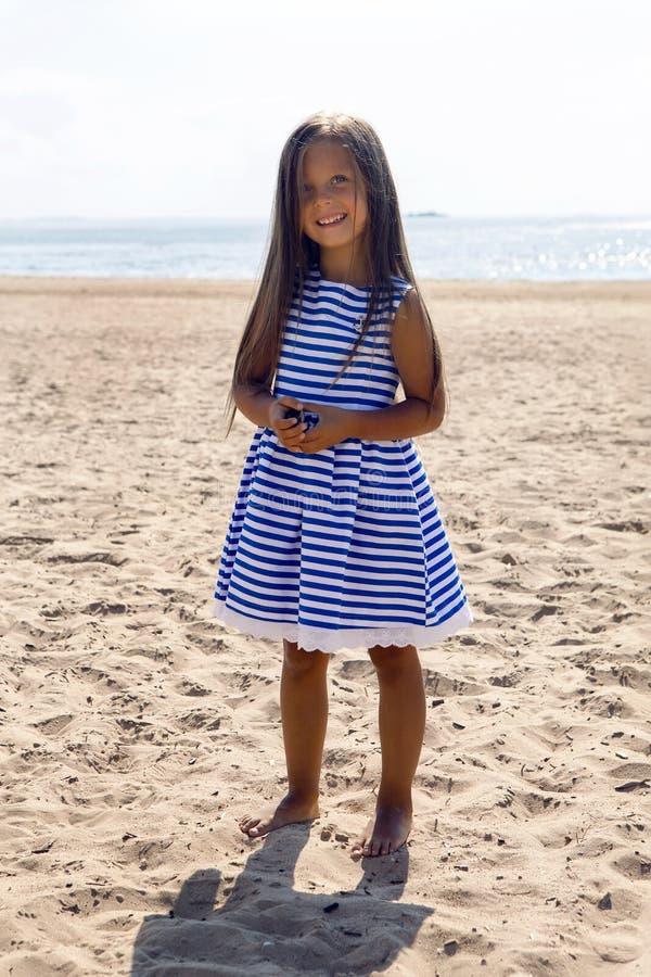 Baby mit dem langen Haar in gestreiftem blauem Kleid lizenzfreies stockfoto