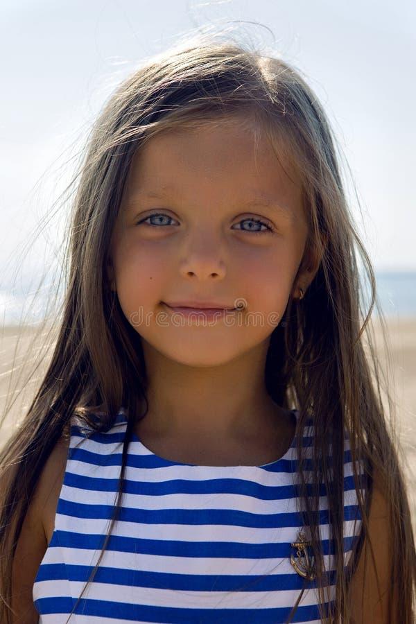 Baby mit dem langen Haar in gestreiftem blauem Kleid lizenzfreie stockfotos