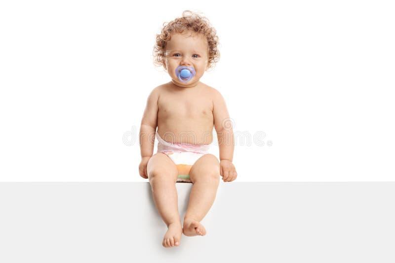 Baby mit einem Friedensstifter, der auf einer Platte sitzt lizenzfreie stockfotos