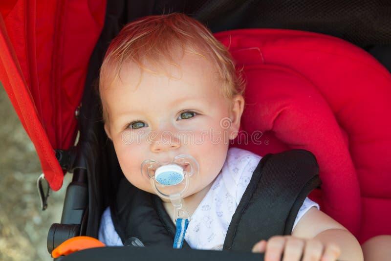 Baby mit einem Friedensstifter in einem Spaziergänger lizenzfreie stockbilder