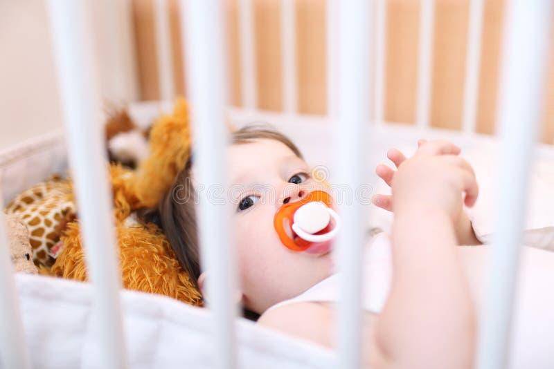 Baby mit Friedensstifter im weißen Bett stockbild