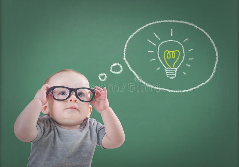 Baby mit Gläsern hat eine Idee lizenzfreie stockbilder