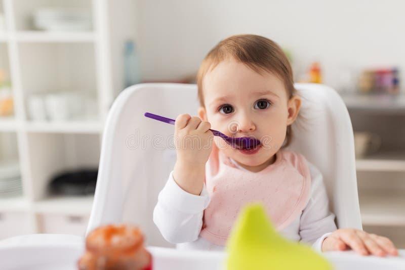 Baby mit Löffel Püree vom Glas zu Hause essend lizenzfreie stockfotografie