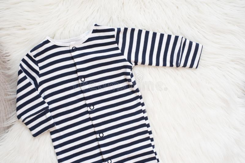 Baby Mockup. Bodysuit On White And Black Stripes. Jumpsuit, Romper On A White Fur Carpet. Newborn Baby Concept. Baby Boy or Girl. Clothes. Copy Space, Top View royalty free stock images