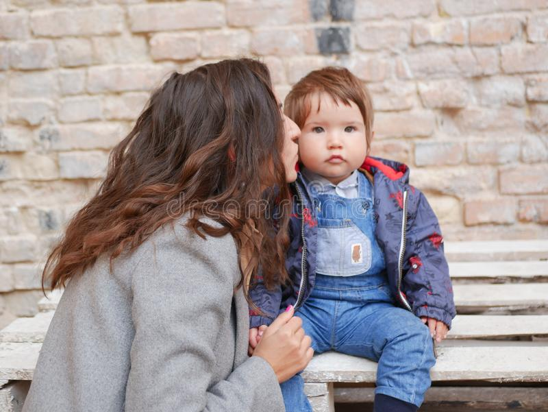 Baby with mom on a brick background. looking at the camera in warm clothes. Happy and young mother sitting on brick background and stock photography
