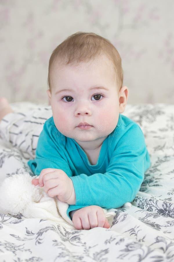 Baby 6 Monate in einer blauen Strickjacke und in gestreiften kurzen Hosen, die auf dem Bett liegen Porträtnahaufnahme der mollige stockfotografie