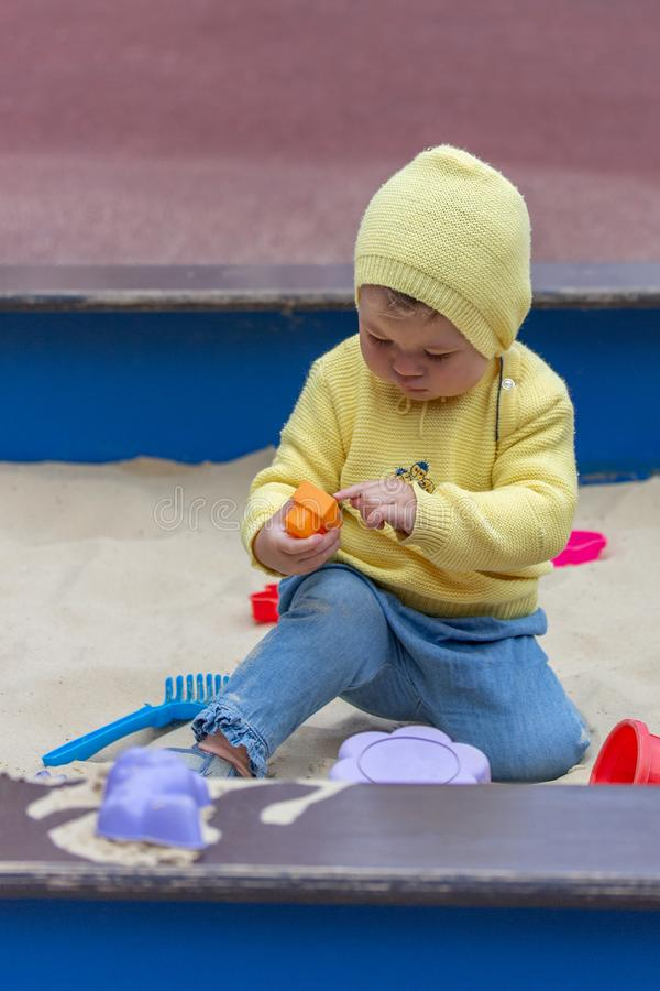 Baby 10 months playing in the sandbox. Child girl boy in a yellow knitted sweater plays with sandbins, vertical portrait Caucasian royalty free stock images