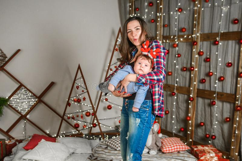 Baby with mother at Christmas. happy family mother and baby little son playing home on Christmas holidays. New Year`s holidays. royalty free stock photos