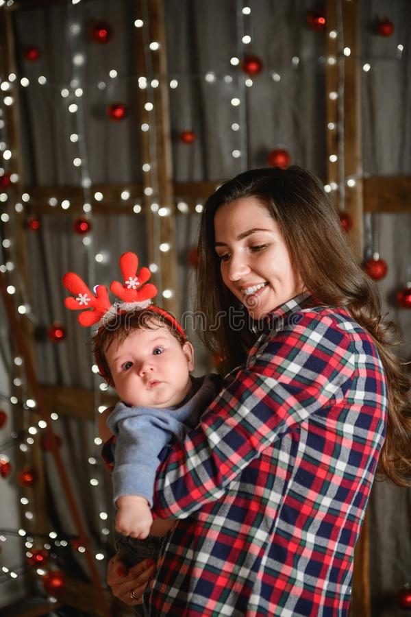 Baby with mother at Christmas. happy family mother and baby little son playing home on Christmas holidays. New Year`s holidays. royalty free stock image