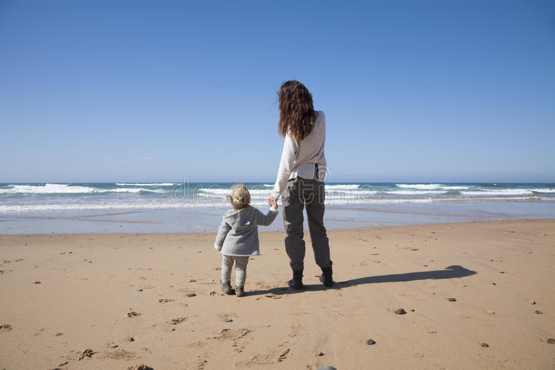 Baby and mother holding hands in beach stock photos