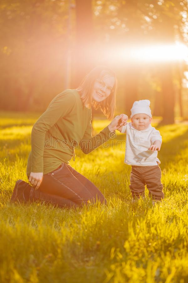 Baby with mother in the park in the rays of sunset. Toddler with mom on the nature outdoors. Backlight. Summertime family scene.  royalty free stock photography