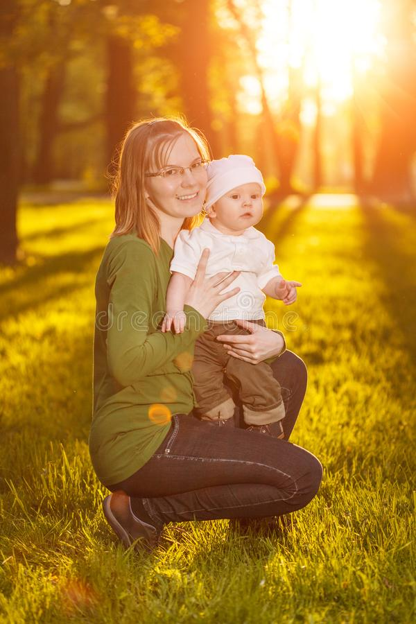 Baby with mother in the park in the rays of sunset. Toddler with mom on the nature outdoors. Backlight. Summertime family scene.  royalty free stock photo