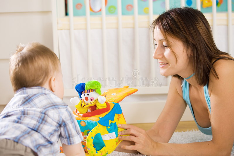 Baby and mother playing stock images