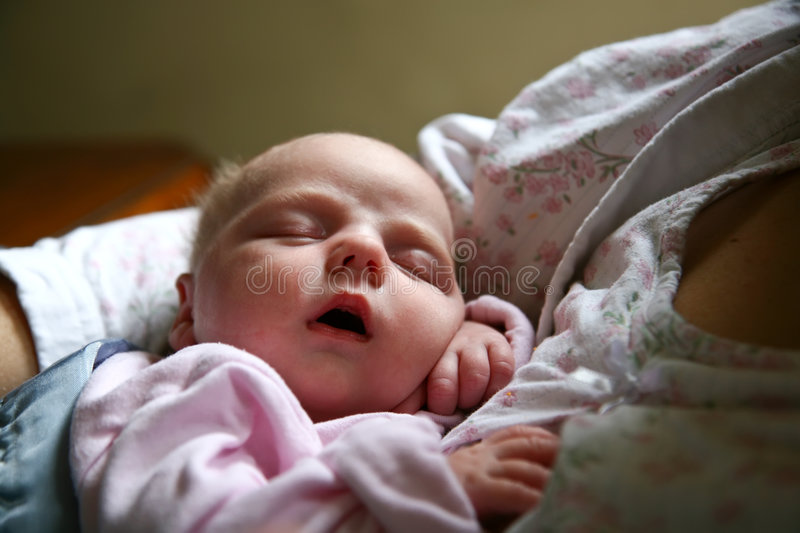 Baby in mother's arms. Infant newborn baby girl sleeping in mother's arms royalty free stock photos