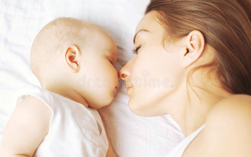 Baby and mother sleeping together. On the bed stock image