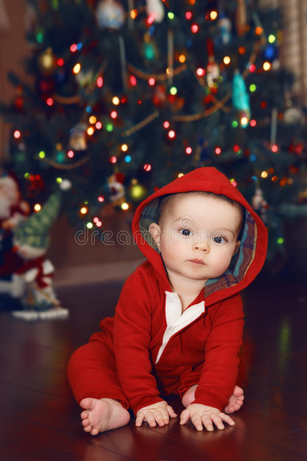 Baby near by New Year Tree, Christmas holidays. Cute adorable Caucasian baby infant with dark black eyes in red costume hoodie sitting by New Year Tree looking stock photo