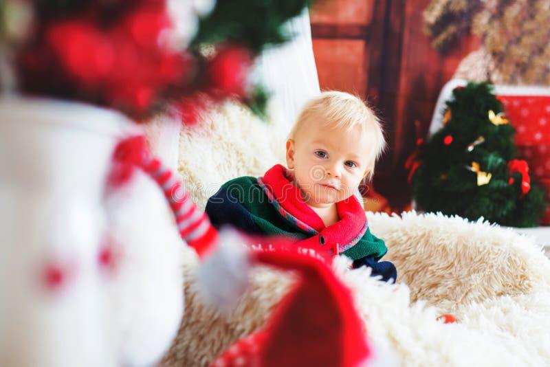 Baby, nettes Kind, tragende Weihnachtsmann-Robe, die im rockin sitzt stockfotos