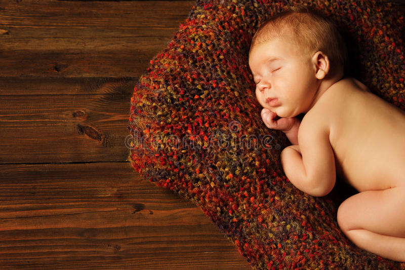 Baby newborn portrait, kid sleeping on brown. Baby newborn portrait, kid sleeping in woolen blanket on brown wooden background royalty free stock photo