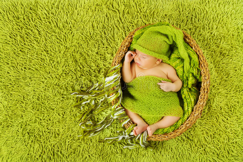 Baby newborn sleeping in woolen hat, green carpet. Baby newborn sleeping in woolen hat inside basket over green carpet background royalty free stock image