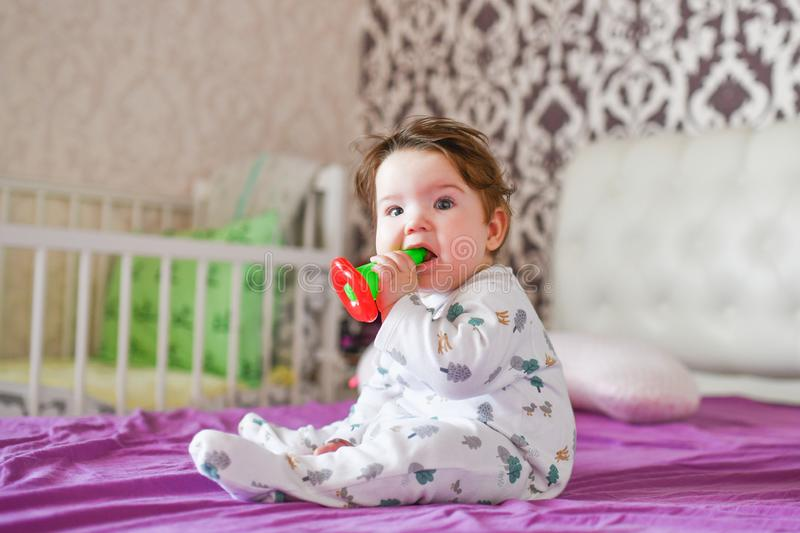 Baby nibbles a toy. closeup portrait little cute girl with big blue eyes with a toy in her hands, nibbles a teether toy stock photos
