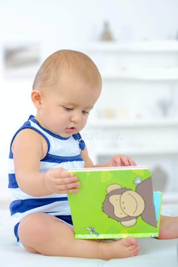 Baby nieuwsgierig met boek royalty-vrije stock afbeeldingen