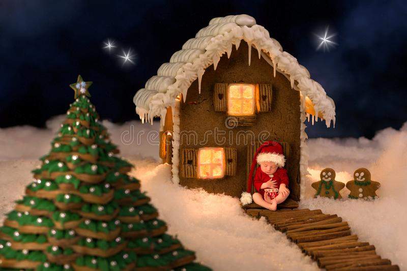 Baby and night sky gingerbread house. Composite image of a newborn baby in front of a christmas gingerbread house in a snow landscape stock photo