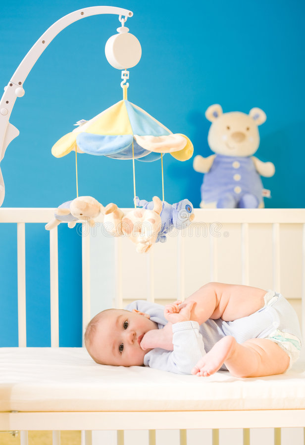 Baby at nursery. Infant baby resting and playing in his little baby bed at nursery. Toys are officially property released royalty free stock photos