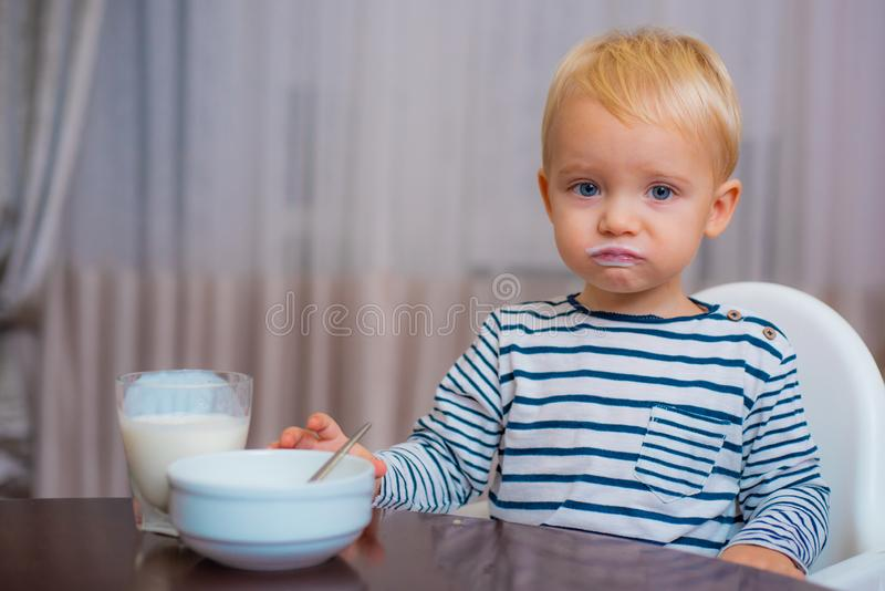 Baby nutrition. Eat healthy. Toddler having snack at home. Boy cute baby eating breakfast. Child eat porridge. Kid cute. Boy blue eyes sit at table with plate royalty free stock image