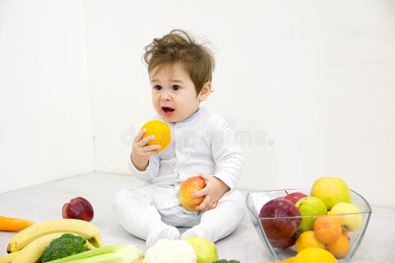 Baby omgav med frukter och grönsaker, sund barnnäring fotografering för bildbyråer