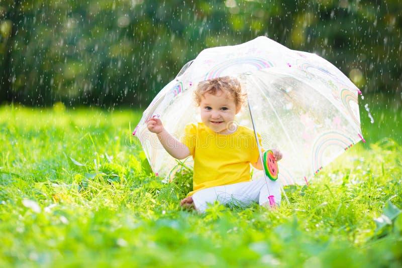 Baby onder paraplu in de zomerregen royalty-vrije stock afbeelding