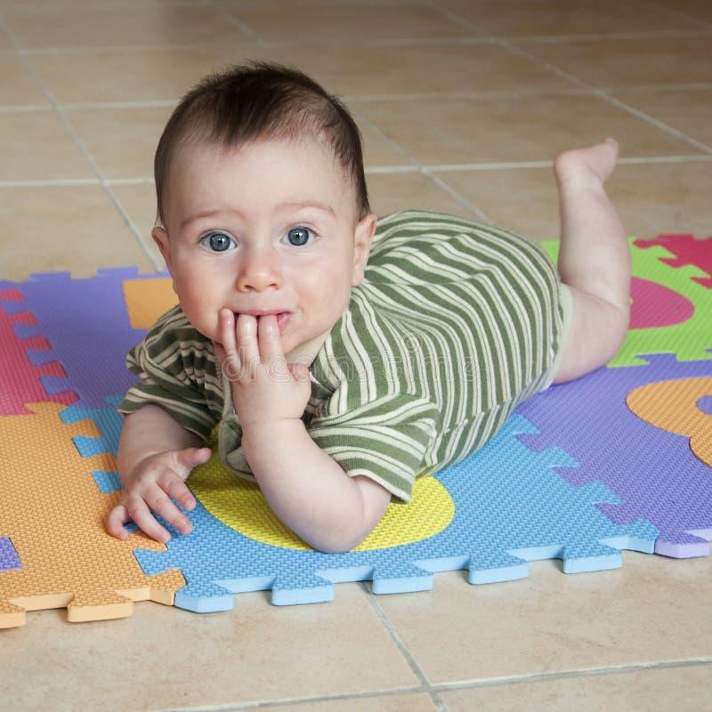 Baby op de vloer stock afbeelding
