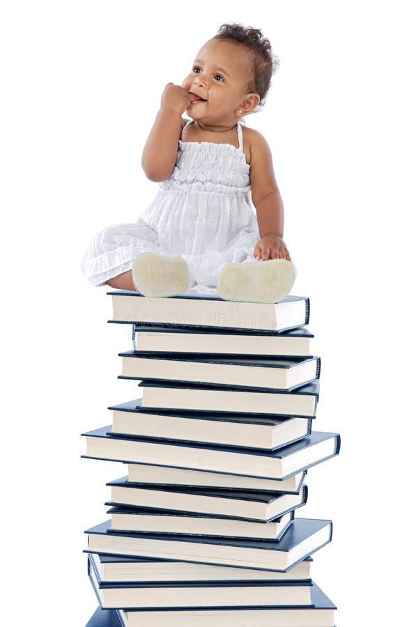 Baby op een boektoren stock foto