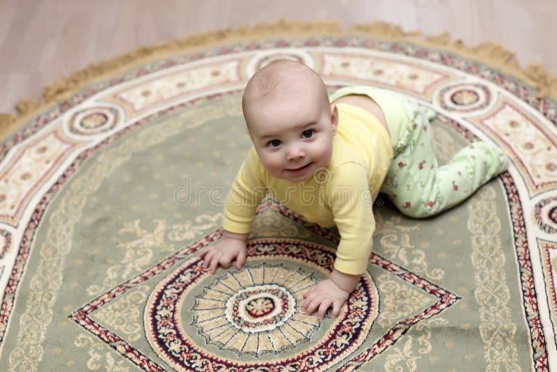Baby op tapijt stock foto's