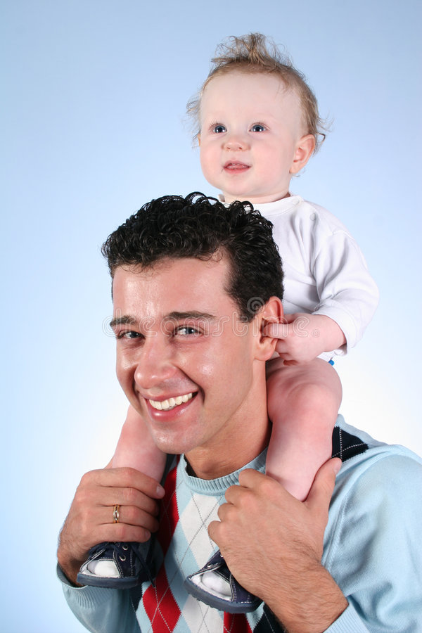 Baby op vadersschouders stock foto