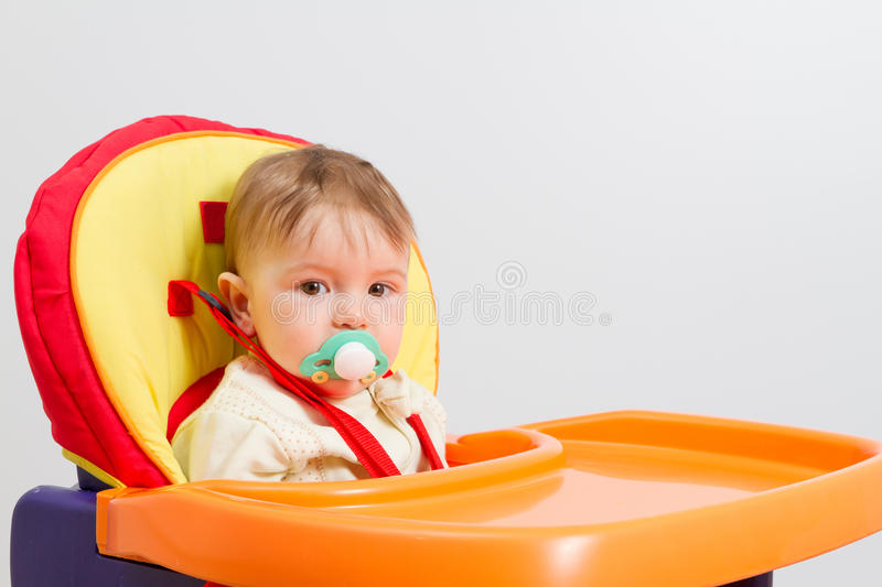 Baby with a pacifier at home stock image
