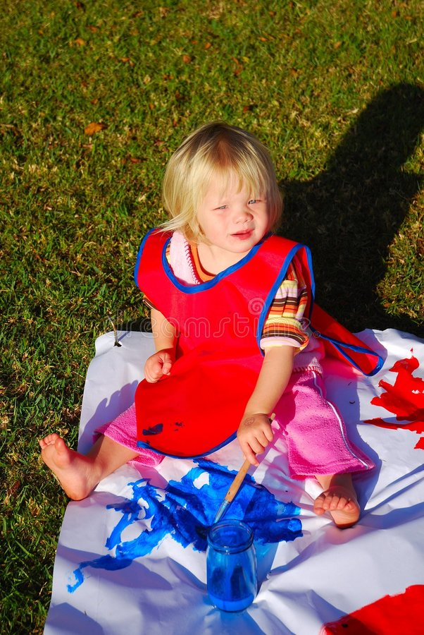 Baby painting outdoors royalty free stock photo