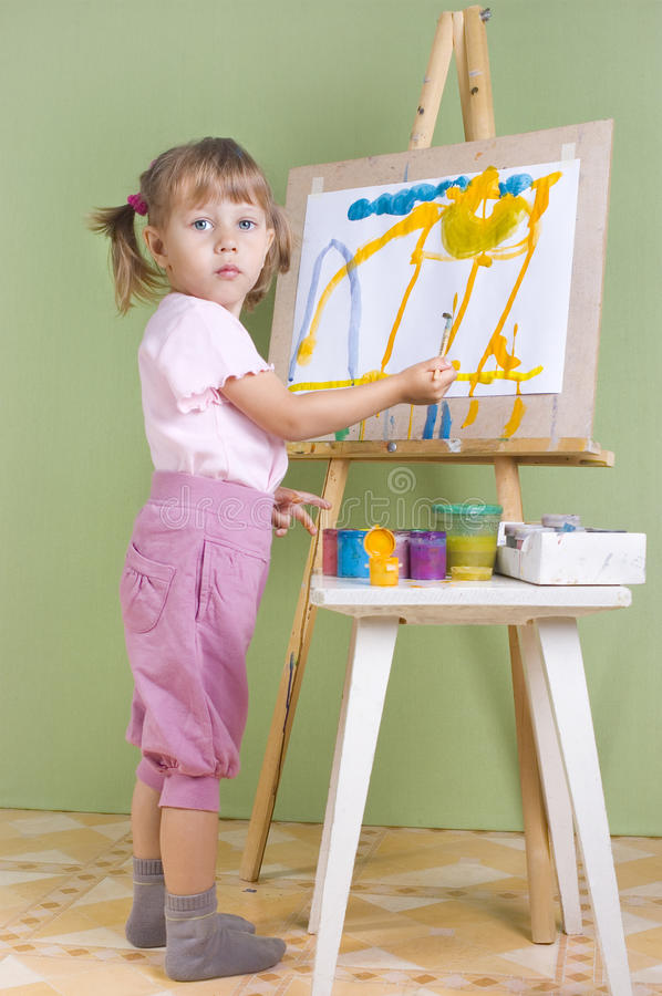 Baby Paints At The Easel Stock Photo