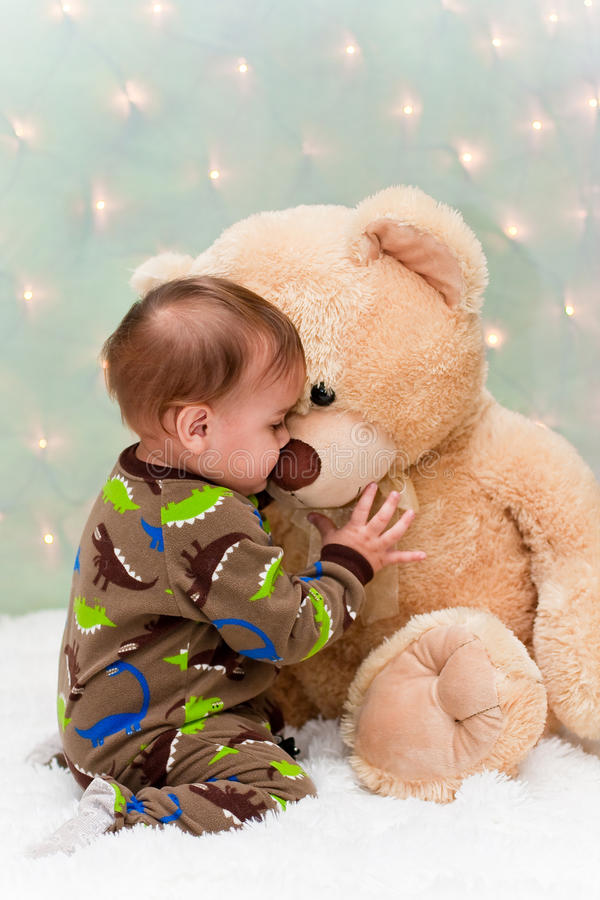 Baby in pajamas kissing teddy bear royalty free stock photo