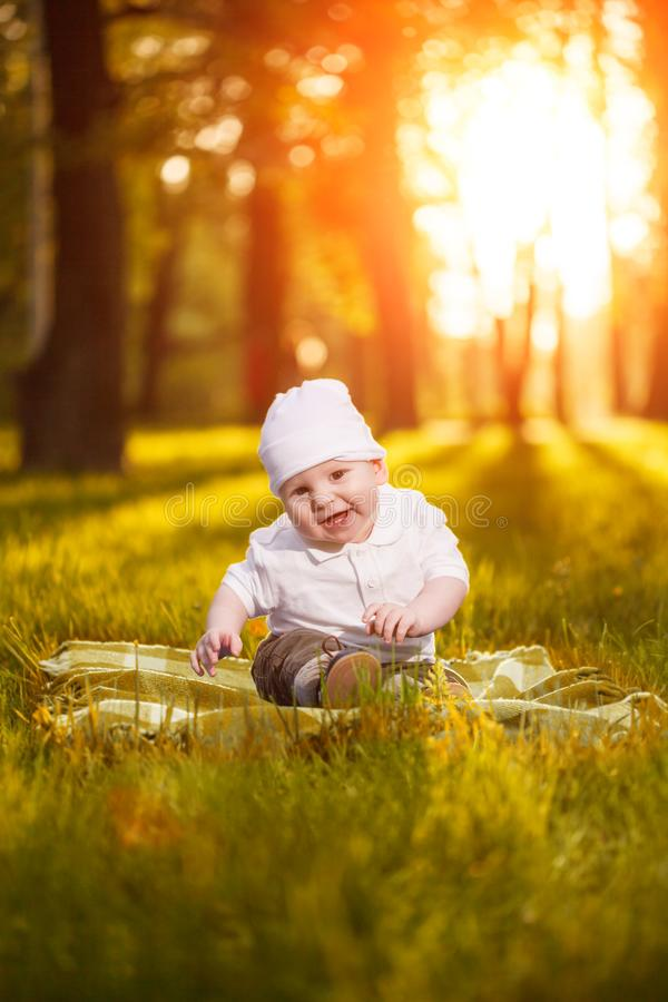 Baby in the park in the rays of sunset. Toddler on the nature outdoors. Backlight. Summertime family scene.  royalty free stock photo