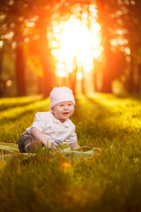 Baby in the park in the rays of sunset. Toddler on the nature outdoors. Backlight. Summertime family scene.  royalty free stock photos