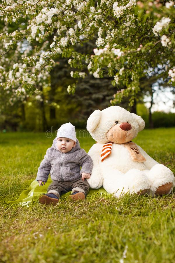 Baby in the park in the rays of sunset. Toddler on the nature outdoors. Backlight. Summertime family scene.  royalty free stock images
