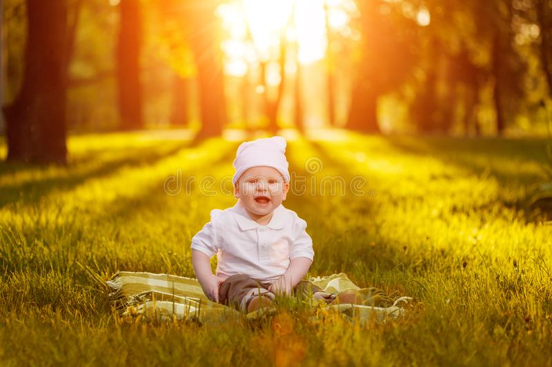 Baby in the park in the rays of sunset. Toddler on the nature outdoors. Backlight. Summertime family scene stock photo