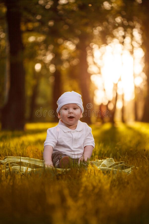 Baby in the park in the rays of sunset. Toddler on the nature outdoors. Backlight. Summertime family scene royalty free stock images
