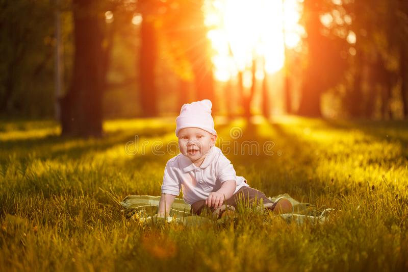 Baby in the park in the rays of sunset. Toddler on the nature outdoors. Backlight. Summertime family scene.  stock photo
