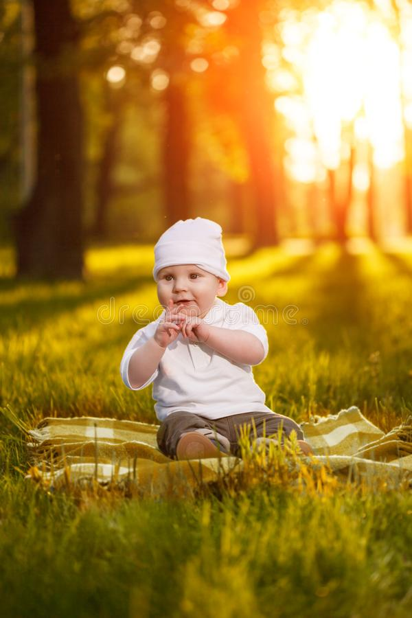 Baby in the park in the rays of sunset. Toddler on the nature outdoors. Backlight. Summertime family scene.  royalty free stock image