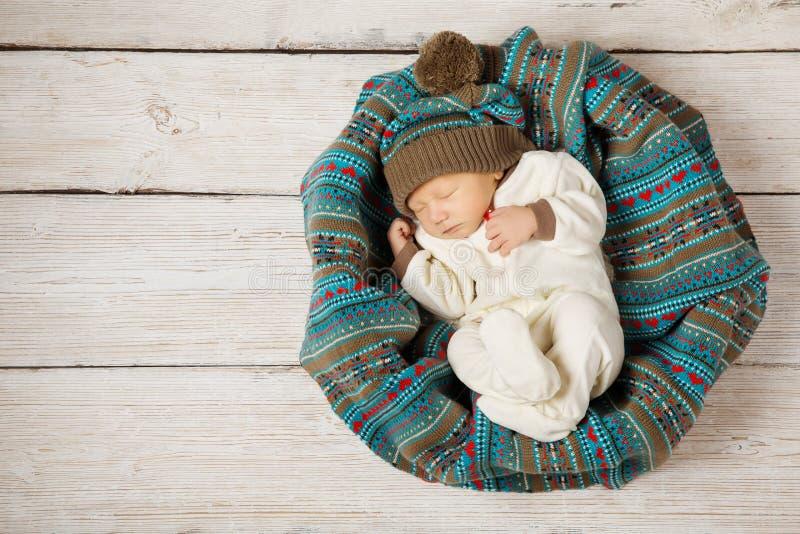 Baby pasgeboren slaap in wollen hoed op wit hout royalty-vrije stock afbeelding