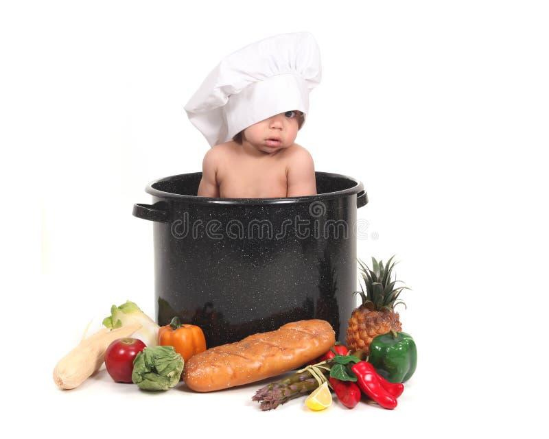 Baby Peeking Through a Chef Hat royalty free stock image