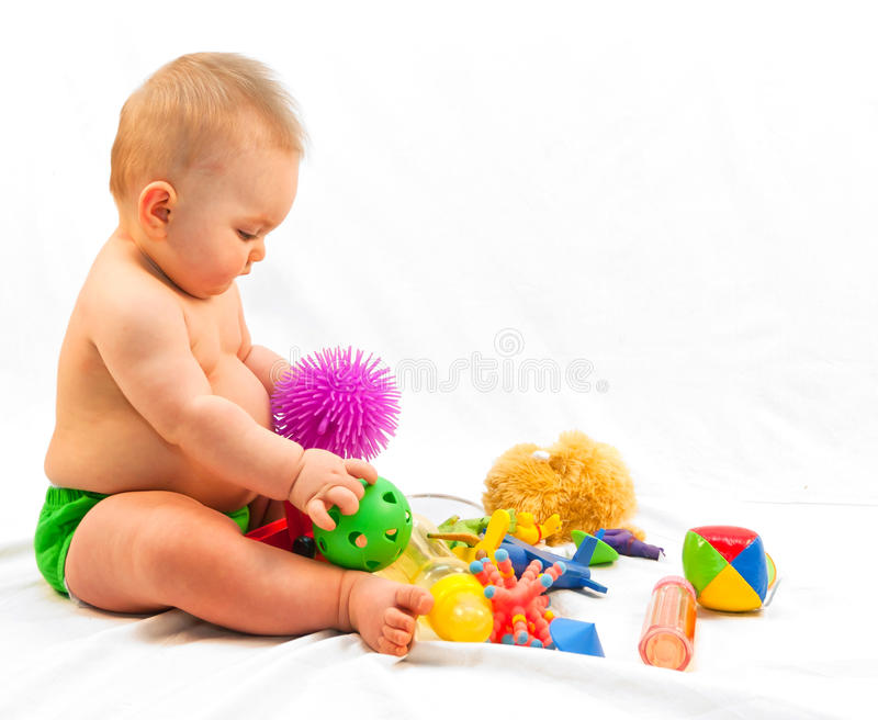 Baby and Pile of Toys. Eight to nine month old baby girl playing with toys. White fabric background stock image