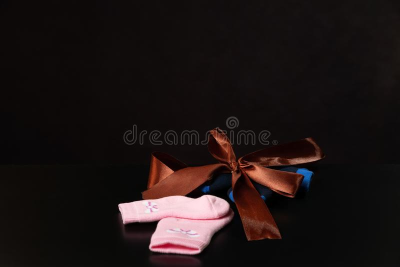 Baby pink and blue socks with a bow are lying on a black table, on a black background. stock photo