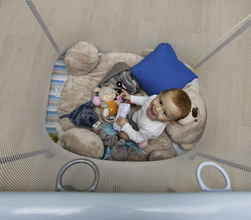 Baby play in playpen. Red hair baby play in a playpen royalty free stock image